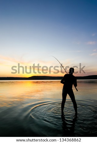 A young man fishing at sunset. The sky is clear and blue. The sun hides behind the horizon. It's quiet around.