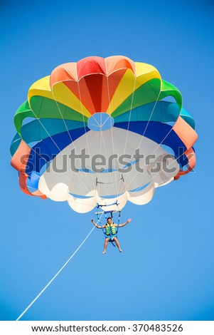 a young man flies on a parachute , blue sky and a parachute otd?h the sea and entertainment - stock photo