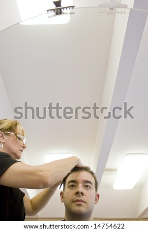 A young man getting his hair cut by a hairdresser at the salon.  Plenty of copy space above. - stock photo