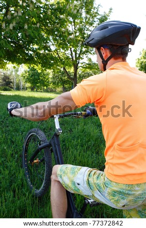 a young man goes for a drive on a sporting bicycle on a background nature, sky, stone and afoot