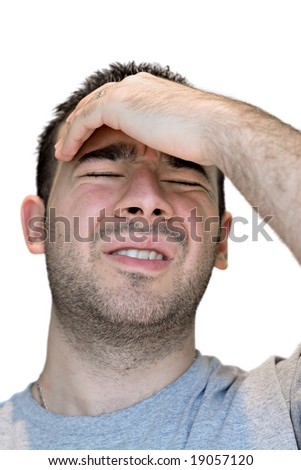 A young man grasps his head in anguish from pain or even stress. - stock photo