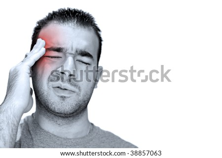 A young man grasps his head in anguish from pain or even stress.  Isolated over white with negative copy space to the right. - stock photo