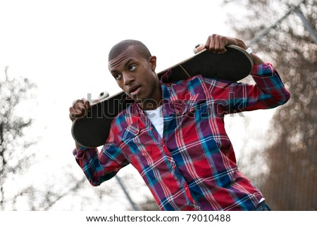 A young man hanging out holding his skateboard on the back of his shoulders over his head. - stock photo