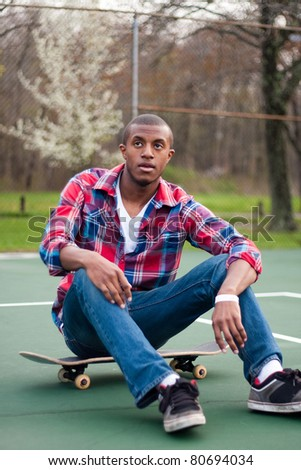 A young man hanging out in the tennis courts sitting on his skateboard. - stock photo