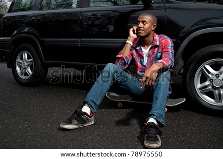A young man hanging out sitting on his skateboard near his vehicle as he talks on his smartphone. - stock photo