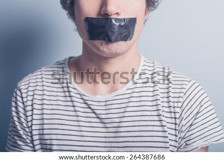 A young man has a big piece of black industrial tape covering his mouth - stock photo