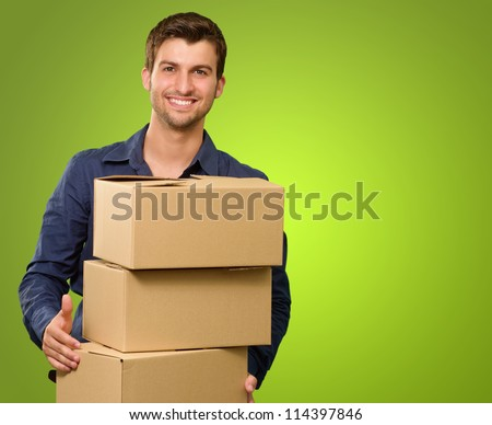 A Young Man Holding A Stack Of Cardboard Boxes On Green Background - stock photo