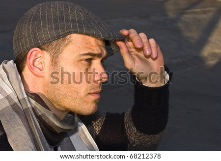 a young man holding his hat staring forward.