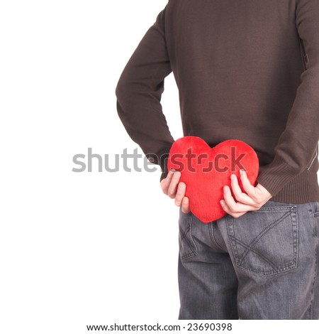 A young man holds a heart shaped pillow behind his back which he gives as a present to his girlfriend for valentines day. Isolated over white. Lot of white copyspace left. - stock photo