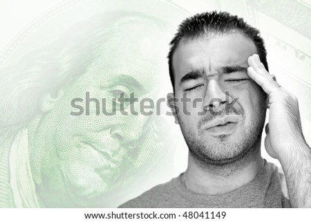 A young man holds his head in anguish as he thinks about his money problems with either debt or unemployment.  A great conceptual image for healthcare or health insurance costs as well. - stock photo