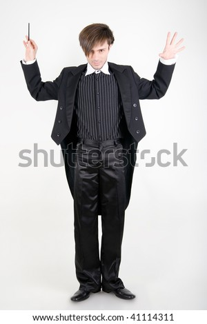 A young man in a black tailcoat with his hands up is looking from under the brows - stock photo