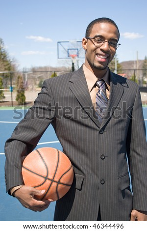 A young man in a business suit at the empty outdoor basketball court. - stock photo