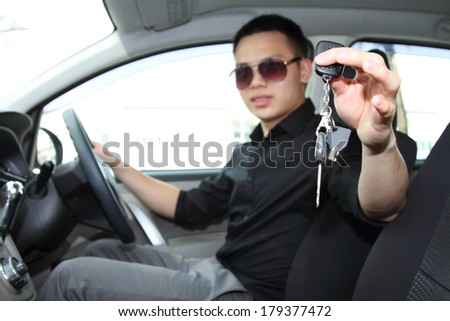 A young man in a car holding up / handing over the car keys. Focus is on the keys - stock photo