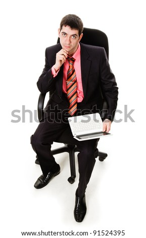 A young man in a suit, sitting in a chair with a laptop, isolated on a white background.