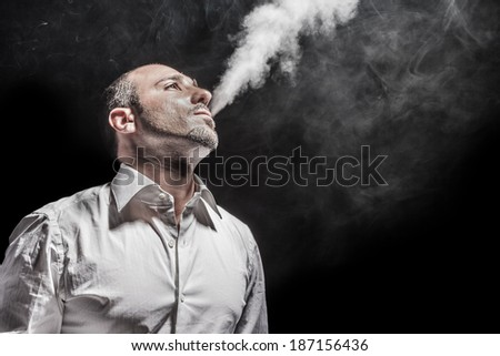 a young man in a white shirt smoking a cigarette over black background