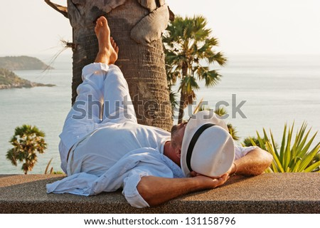 A young man in a white suit lies on the waterfront