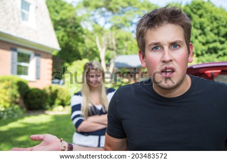 A young man in an argument with his wife, looks to the camera audience for support  - stock photo