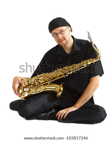 A young man in black clothes, black cap, wearing glasses, sitting and holding his saxophone in his lap, looking into camera - isolated on white - stock photo