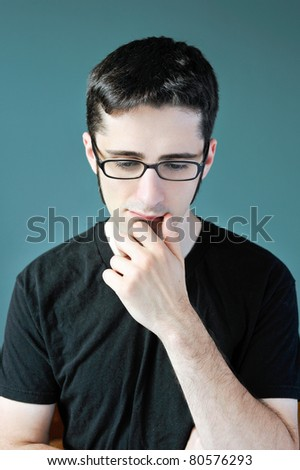 A young man in deep thought with his hand to his chin. - stock photo