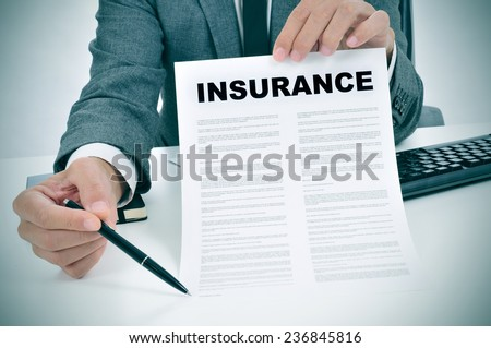 a young man in suit in his office showing an insurance policy and pointing with a pen where the policyholder must to sign - stock photo