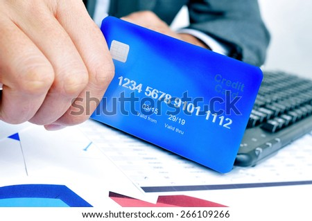 a young man in suit shopping online with a credit card - stock photo