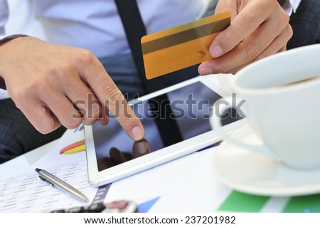 a young man in suit shopping online with a credit card via a tablet computer - stock photo