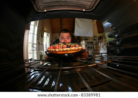 a young man is excited about the fruit tart he just baked in his oven - stock photo
