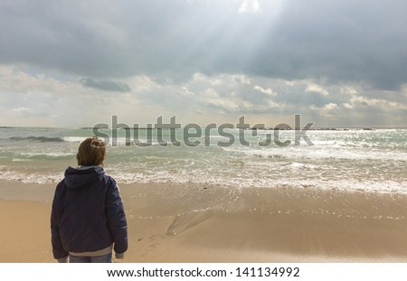A young man is looking at sun rays through the clouds on beach in a sunny winter day - stock photo