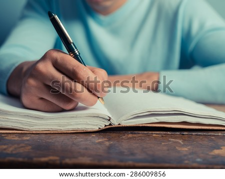 A young man is sitting at a table and is writing in a notebook - stock photo