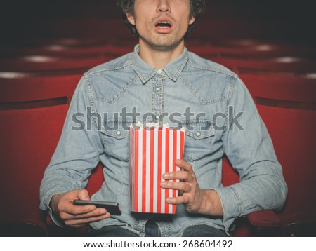 A young man is sitting in a cinema and is watching a film while holding his smartphone and a bucket of popcorn - stock photo