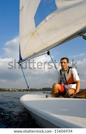 A young man is sitting in a sailboat.  He is smirking and looking away from the camera.  Vertically framed shot.
