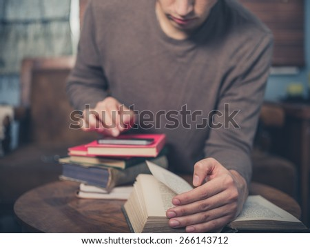A young man is sitting on a sofa surrounded by books and is using his smartphone - stock photo