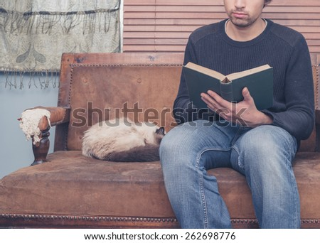 A young man is sitting on a sofa with a cat and is reading a big book