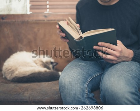 A young man is sitting on a sofa with a cat and is reading a big book - stock photo