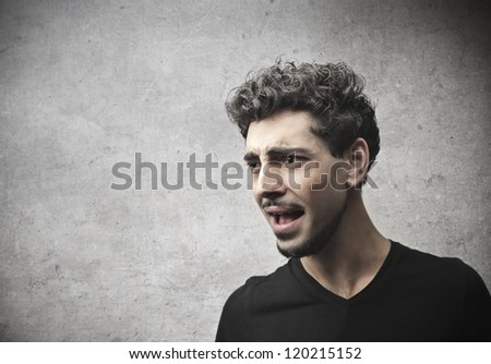 A young man is unpleasantly surprised by something - stock photo