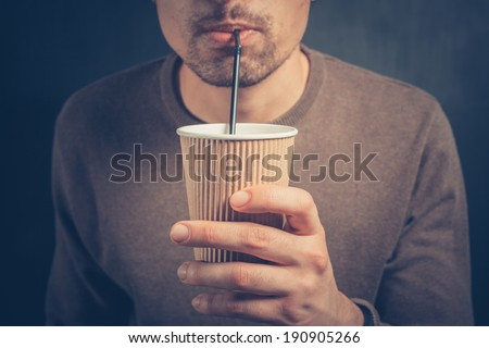 A young man is using a straw to drink from a paper cup - stock photo