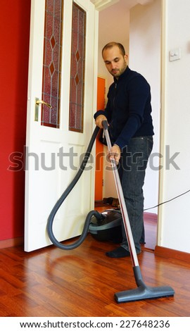 A young man is vacuuming the living room