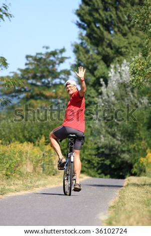 A young man is waving from the bike cheerfully - stock photo