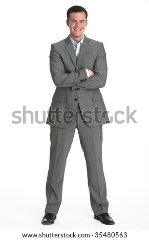 A young man is wearing a business suit and smiling at the camera.  Vertically framed shot. - stock photo