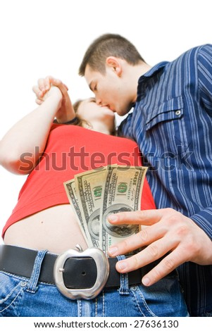 A young man kissing a beautiful young woman, putting money in her pants - stock photo