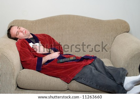 A young man laying on a sofa in his bathrobe, feeling ill because he has the flu - stock photo
