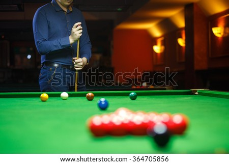 A young man lines up his shot as he breaks the balls for the start of a game of snooker - stock photo