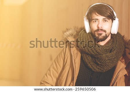 a young man listens to music in an urban image of modern life warm tones style toned - stock photo