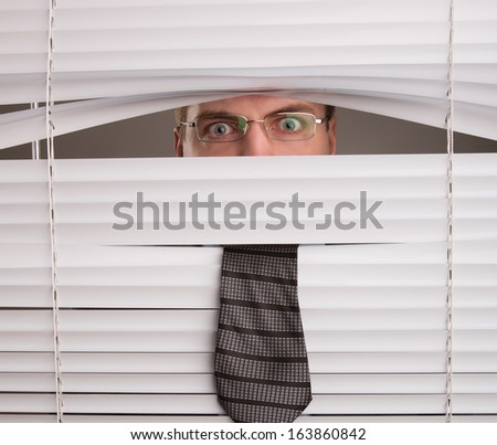 A young man looking through window blinds - stock photo