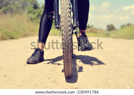 a young man on a mountain bike on a dirt road - stock photo
