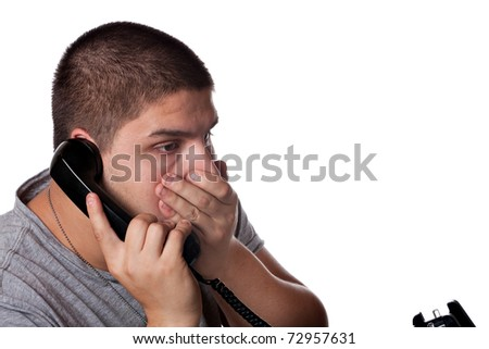 A young man on the phone places his hand on his mouth in disbelief of the news he has just heard. - stock photo