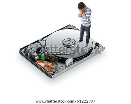 a young man on top of a hard drive covering his face with hands - stock photo