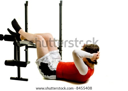 A young man performing sit-ups over a white background. - stock photo