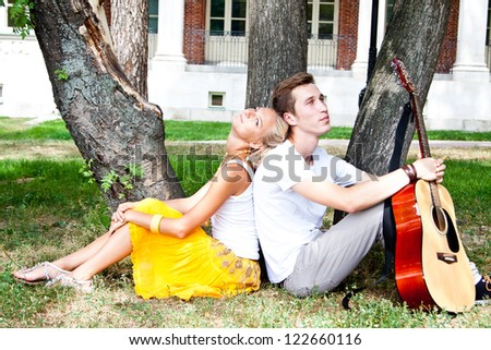 A young man plays guitar in the park beautiful woman - stock photo