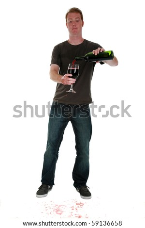 a young man pours a glass of red wine, isolated on white
